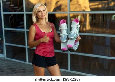 woman keeps kangoo jumping boots and smiling at camera. Fitness girl shows thumps up