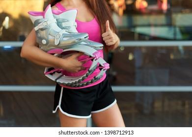 woman keeps pink kangoo jumping boots in hand and shows thumbs up. Close up shot