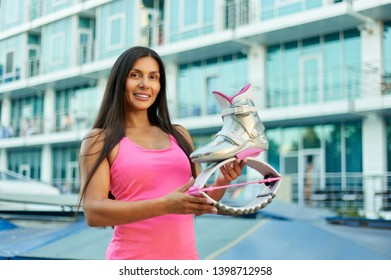 woman keeps pink kangoo jumping boots and smiling at camera. Happy Fitness woman. Sport training concept