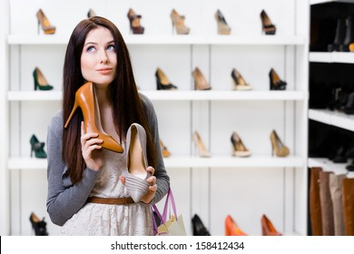 Woman keeps two stylish pumps in the shopping mall and can't choose the one for her