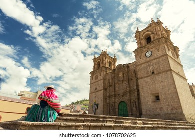 Woman with keperina (bag on her back) sitting on the steps of the Cathedral of Puno (Peru)