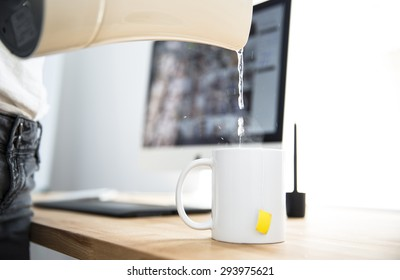 Woman with kettle pouring water in a cup at office