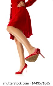 woman is kicking. girl in red dress kicks with her leg in high shoes to camera on white background