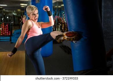 Woman kicks bag intense kickboxing muay thai training amateur beginner martial arts class