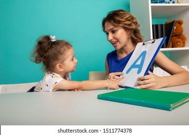 Mujer con niña entrenando un discurso juntos sentada en la habitación blanca.