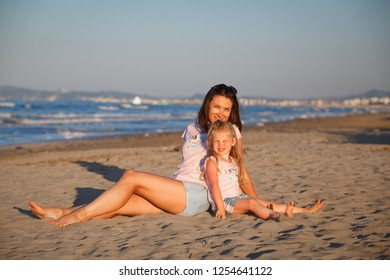 Woman and kid in the same t-shirs posing on beach. Smiling mother with daughter in Rimini. Famaly vacation background.