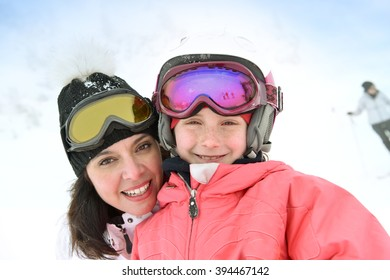 Woman with kid in ski outfit enjoying wintertime
