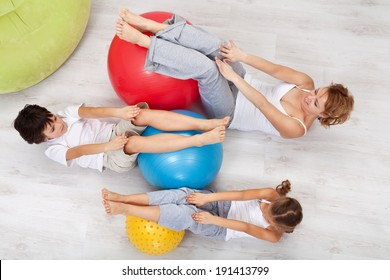 Woman and kids exercising together at home - with large gymnastic walls, top view