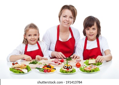 Woman and kids making creative food creature sandwiches together - isolated
