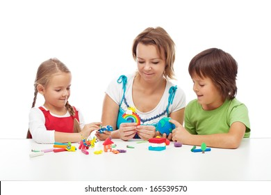 Woman and kids playing with colorful clay molding different shapes