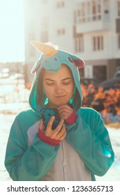 woman in kigurumi unicorn costume use mobile phone with unhappy face  on the street