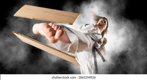 Woman in kimono practicing. Fighter concept. Breaking board. Smoke background