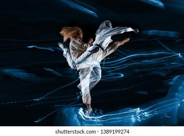 Woman in kimono practicing taekwondo. Double exposure.Modern Korean martial art similar to karate