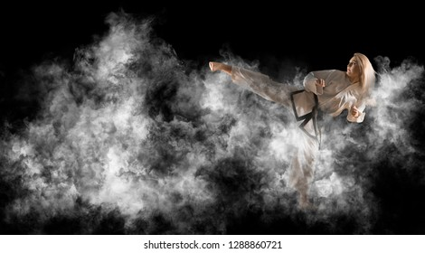 Woman in kimono practicing taekwondo. Smoke background