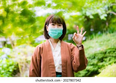 仮面を着て温泉の中を旅する着物を着た女性