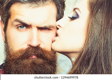 Woman kiss hipster with long beard, love. Sensual woman with makeup skin and bearded man. Couple in love and family concept. Beauty salon and barber shop. Skincare and hair care concept.