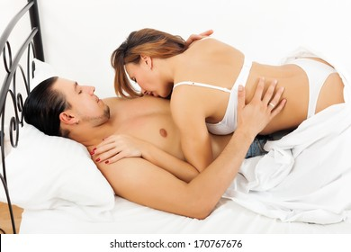 woman kissing her man in chest in bed