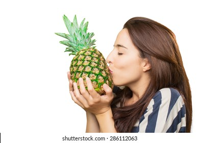 Woman kissing a pineapple. Over white background