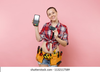 Woman with kit tools belt full of variety instruments holding bank payment terminal to process and acquire credit card payments isolated on pink background. Female in male work. Renovation concept