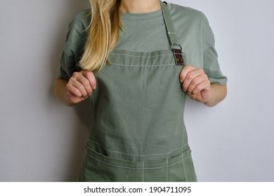 A woman in a kitchen apron. Chef work in the cuisine. Cook in uniform, protection apparel. Job in food service. Professional culinary. Green fabric apron, casual clothing. Handsome baker posing