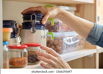 Woman in the kitchen with can of dry mint, food storage, pantry.