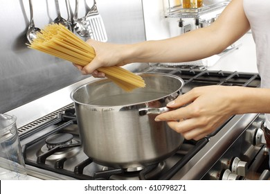 WOMAN IN KITCHEN COOKING SPAGHETTI