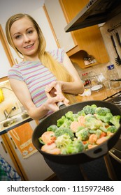 Woman in kitchen cooking stir fry frozen vegetables on pan and tasting. Girl frying making delicious dinner food meal.