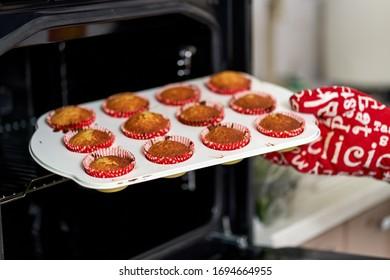 Femme avec gant de cuisine sortant des muffins du four