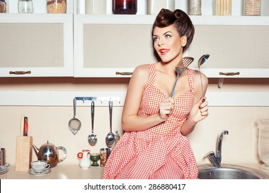 The woman in the kitchen. In the hands holding tools for cooking food. She flirts.