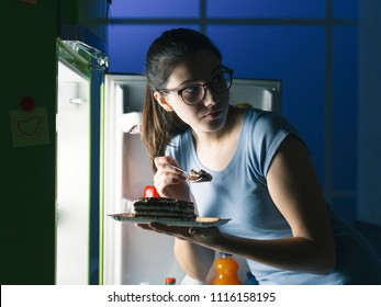 Woman in the kitchen having a late night snack, she is taking a delicious dessert from the fridge, diet fail concept
