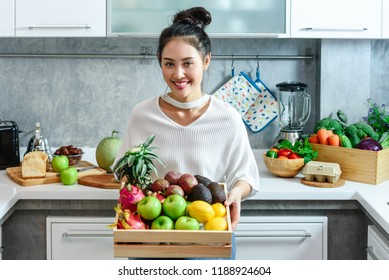 Woman in kitchen with holding a box of various kind of fruits and vegetables that all are good for health and no meat, vegan lifestyle
