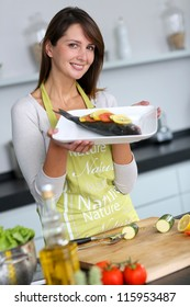 Woman in kitchen holding fish dish
