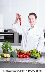 Woman in the kitchen holding hot chili paprika