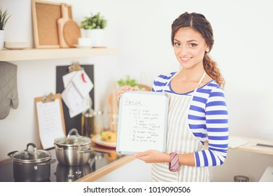 Woman in the kitchen at home, standing near desk with folder. Woman in the kitchen