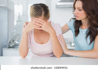 Woman in the kitchen looking at her overwhelmed friend