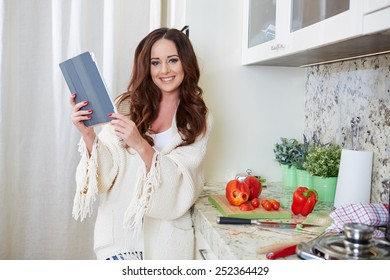Woman in kitchen looking at recipe on tablet