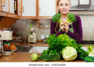Woman in kitchen with many green leafy vegetables, fresh produce on counter. Young housewife holding broccoli in hand. Healthy eating, cooking, vegetarian food, dieting and people concept.