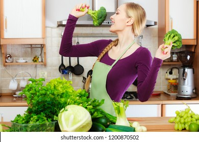 Woman in kitchen with many green leafy vegetables, fresh produce on counter. Young housewife having fun holds broccoli., singing. Healthy eating, cooking, vegetarian food, dieting concept.