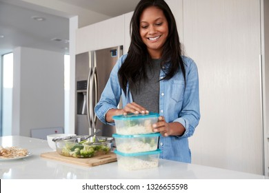 Woman In Kitchen Preparing High Protein Meal And Putting Portions Into Plastic Containers