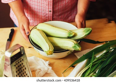 The woman in the kitchen preparing a meal of fresh ripe green stuff long zucchini. Country style. Women's hands. Vegetable dish. Marinating squash before cooking