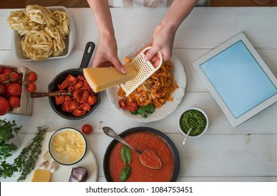 Woman in the kitchen preparing tasty, homemade pasta in cozy kitchen. Female hands grating cheese. Pasta with pesto sauce, basil, cherry-tomatoes and garlic on old grunge white table, top view.
