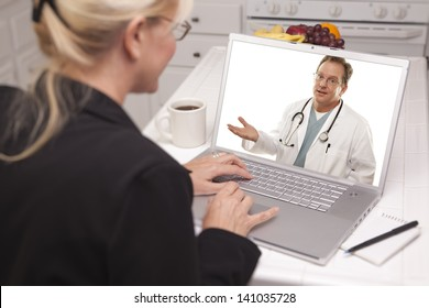 Woman In Kitchen Using Laptop - Online Chat with Nurse or Doctor on Screen.