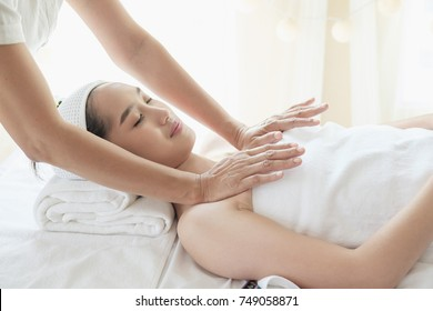 The woman is kneading the chest to tighten the chest muscles. Which is part of Thai massage.
