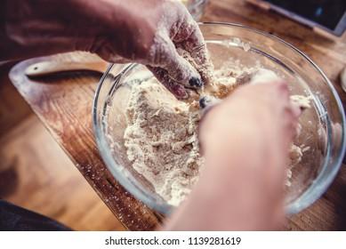 Woman kneading dough in glass bowl