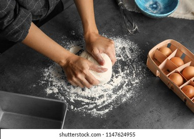 Woman kneading dough for pastry on table