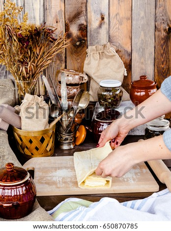 Woman is kneading homemade puff pastry dough. Female baker hands rolling dough with pin.