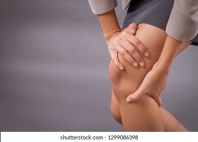 woman with knee joint pain symptoms, closeup hand holding injured knee; portrait of asian woman suffering from knee pain injury with surgical cut scar; tan skin asian young adult woman model