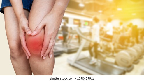 A woman with knee pain with fitness gym background