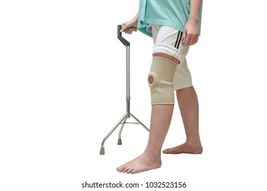 Woman in knee support walking on cane ,isolate on white