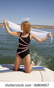 A woman kneeling on the back of a boat holding out her white sarong in the breeze.